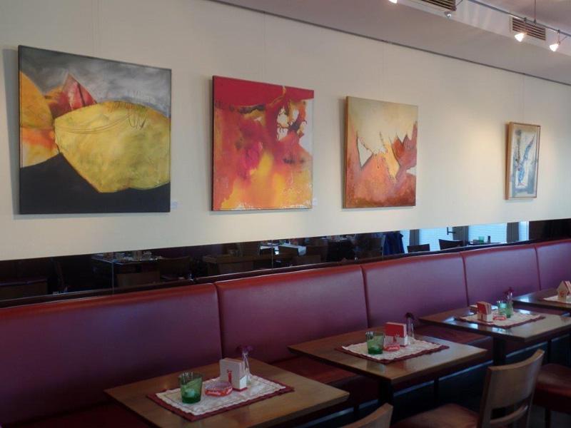 Foto: Tische und Bänke in einem Café. An der Wand hängen Bilder.