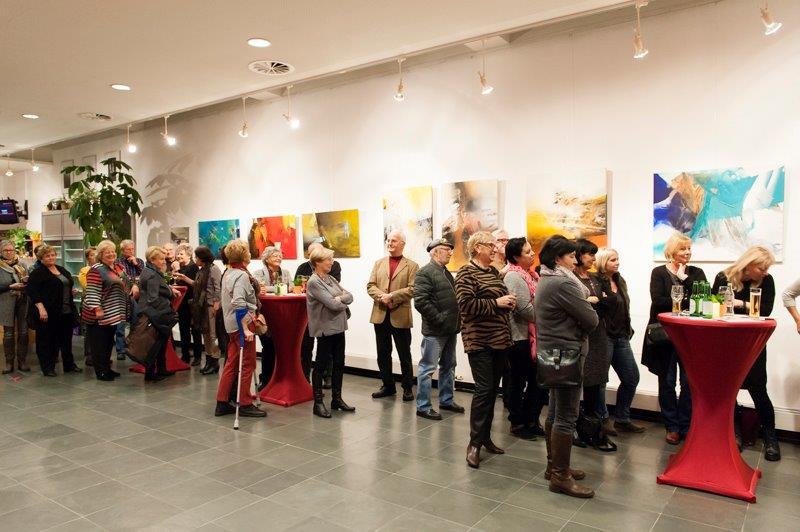 Foto: Ein großer Raum mit Bildern. Die Gäste betrachten die Bilder.